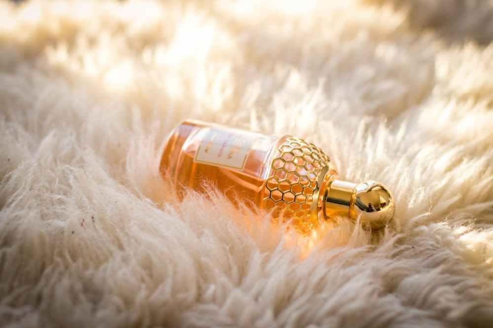 clear perfume bottle on white fur textile